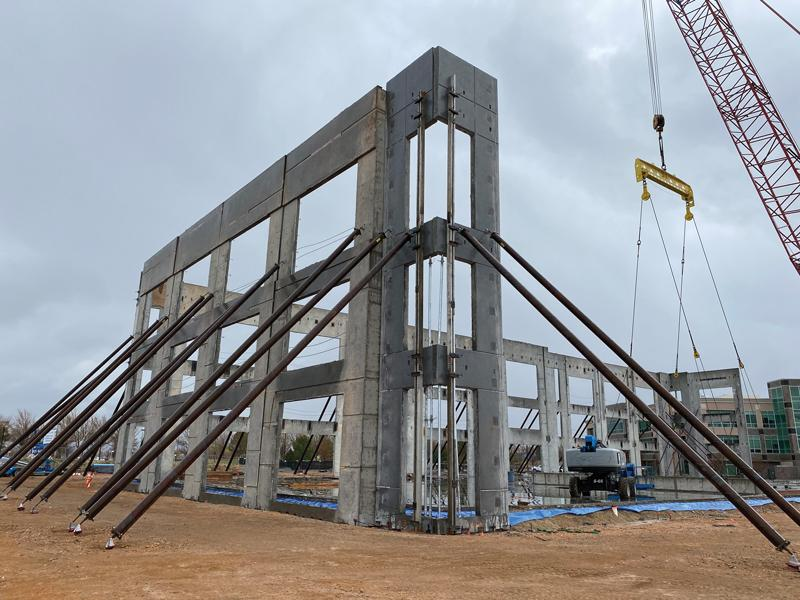 3-story tilt-up panel braced to the exterior using temporary helical piers.
