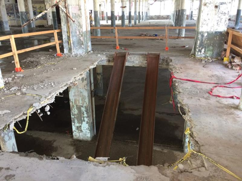 Figure 18. Vehicle access opening cut in the slab during demolition required the installation of shoring posts in the surrounding compromised bays.
